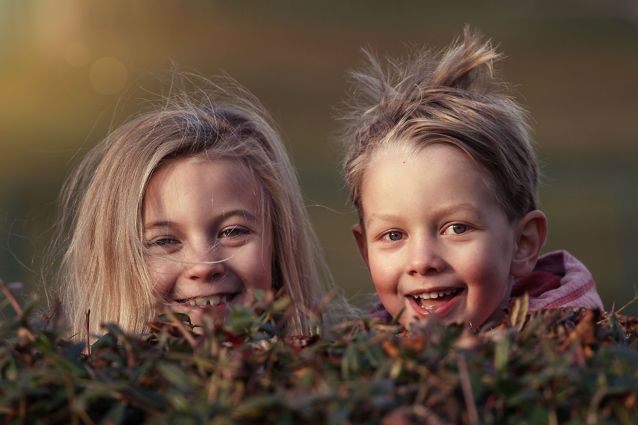 Two children smiling over a plant.