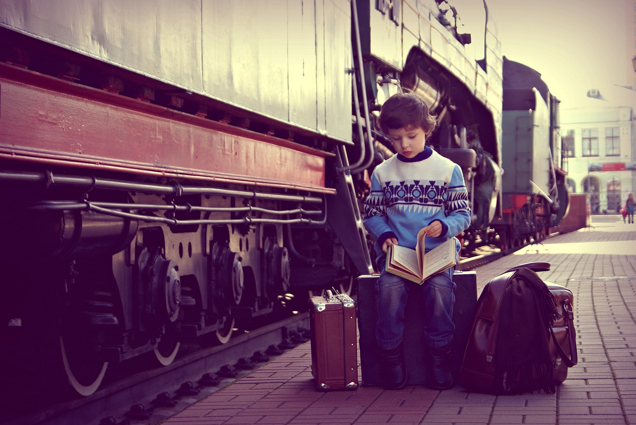 Young boy sitting on a train platform reading.