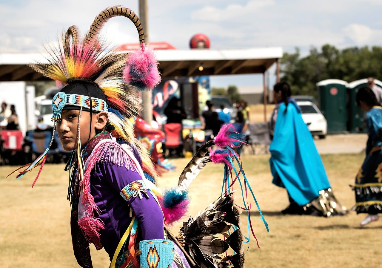 Native American child dressed in traditional dance regalia at a pow wow.