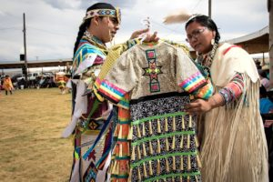 Two Native American peoples comparing clothes for sale at a traditional pow wow.