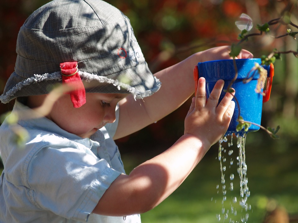 A child filling a bucket with water.