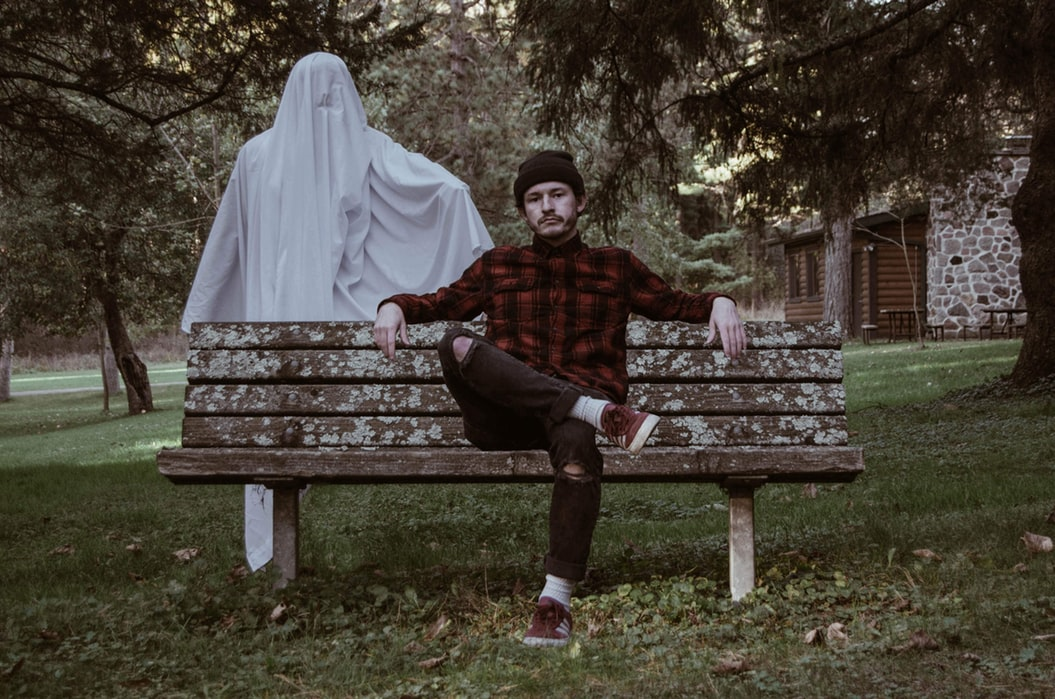 A man sitting on a bench with a ghost behind him.