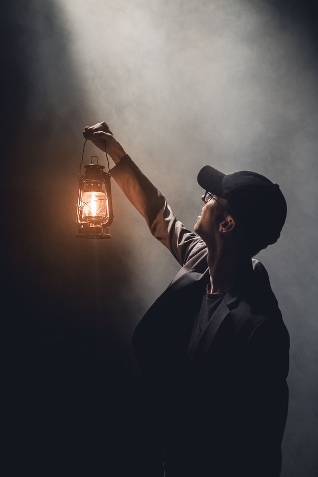 A man holding up a lantern.